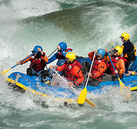 A raft goes through a big rapid on the Karnali river whilst on Karnali River Rafting in west Nepal.